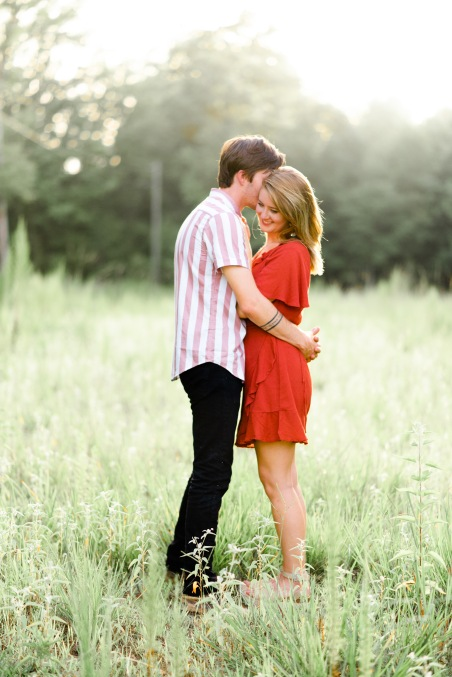 engagement session, love, couple photography, wedding photography, engaemnt photography, green field, red dress, mens striped shirt, outfit, brmingham wedding photograher, mississippi wedding photographer, field of grass, kiss, sunset,